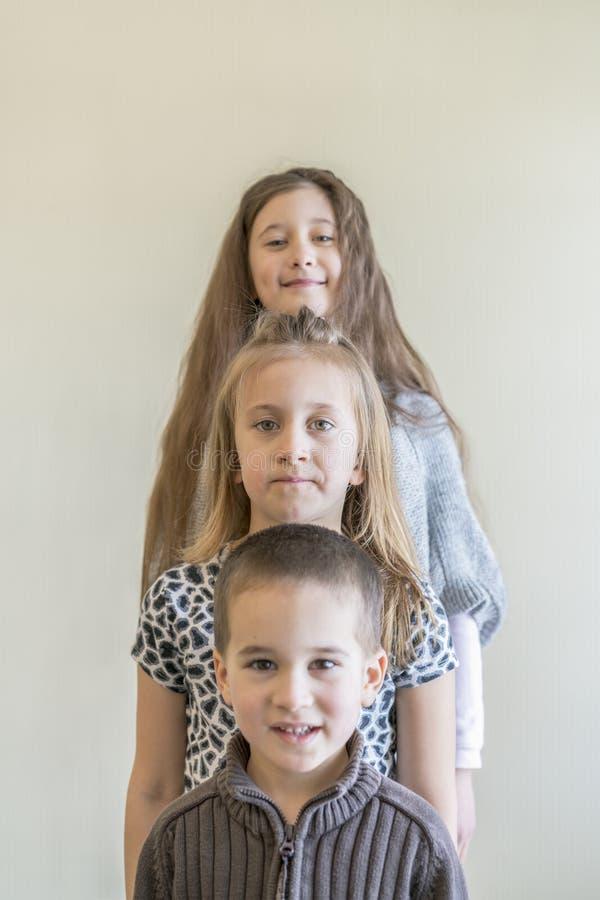 Drie kinderen bevinden zich op een rij Twee meisjes en een jongen Broer en twee zusters royalty-vrije stock foto's