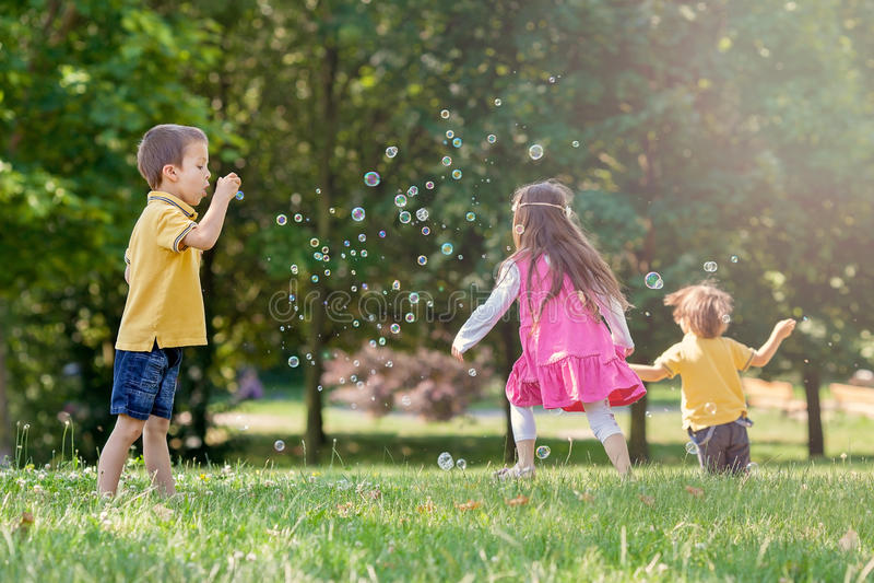 Drie kinderen in de park blazende zeepbels en het hebben van pret stock afbeelding