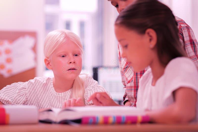 Drie kinderen die bij de schoolles zitten royalty-vrije stock afbeeldingen