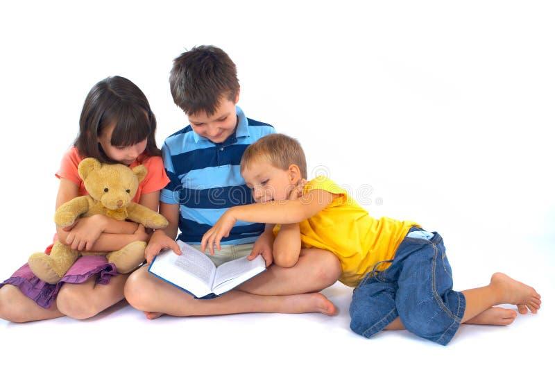 Drie kinderen die boek lezen stock afbeelding
