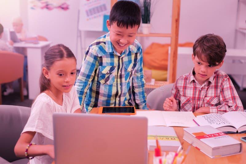 Drie kinderen die Chinees leren bij laptop royalty-vrije stock afbeeldingen