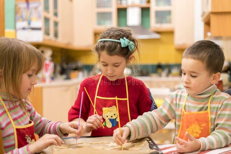 Drie kinderen die koekjes van deeg vormen Twee meisjes en een jongen royalty-vrije stock fotografie