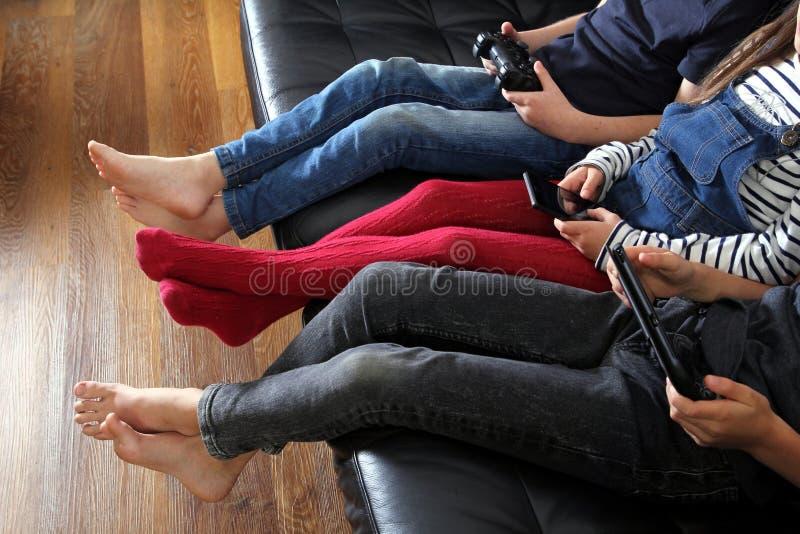Drie kinderen die met elektronische apparaten spelen - tablet, smartph stock foto