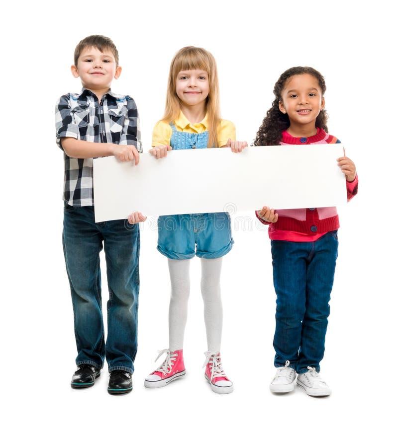 Drie kinderen die met open monden leeg blad van document houden royalty-vrije stock afbeelding