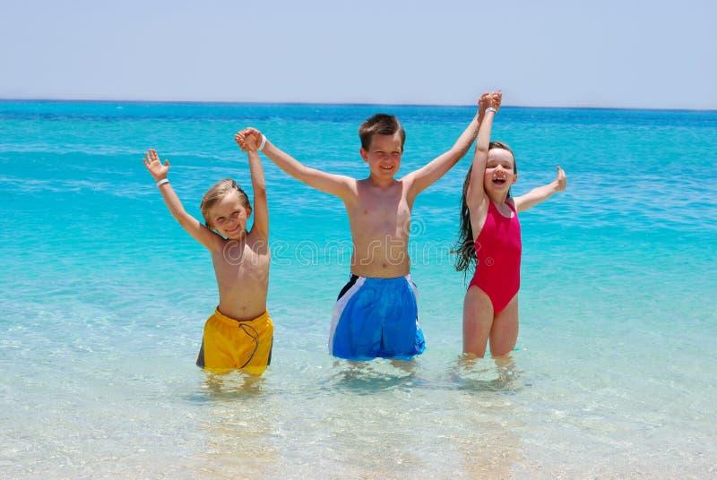 Drie kinderen die in Oceaan waden stock afbeelding