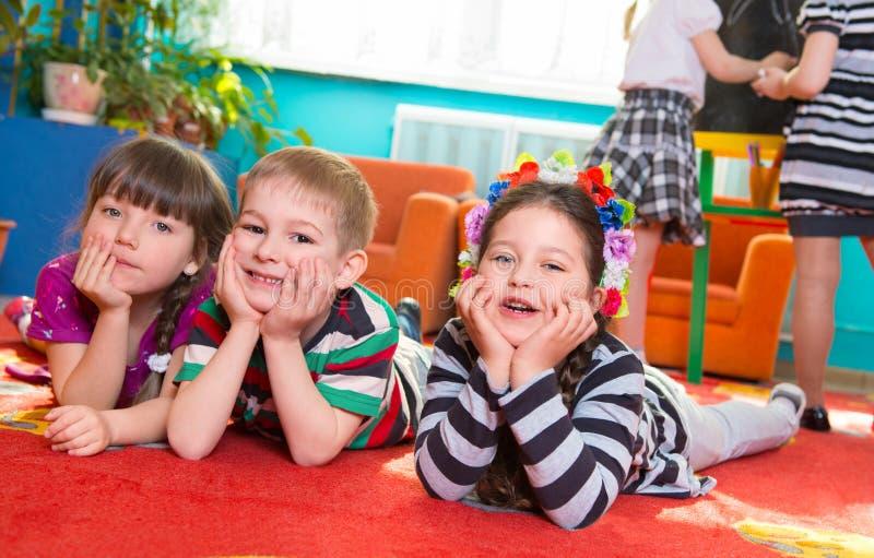 Drie kinderen die op vloer met handen onder wangen liggen stock afbeeldingen
