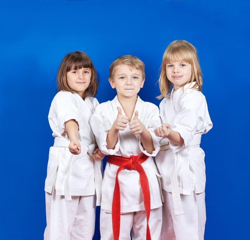 Drie kinderen die zich in karate bevinden rekken en super vinger tonen stock fotografie