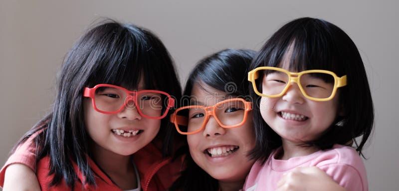Drie kinderen dragen grote oogglazen stock fotografie