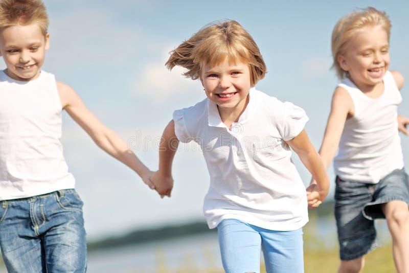 Drie kinderen lopen op een gekleurde achtergrond stock fotografie