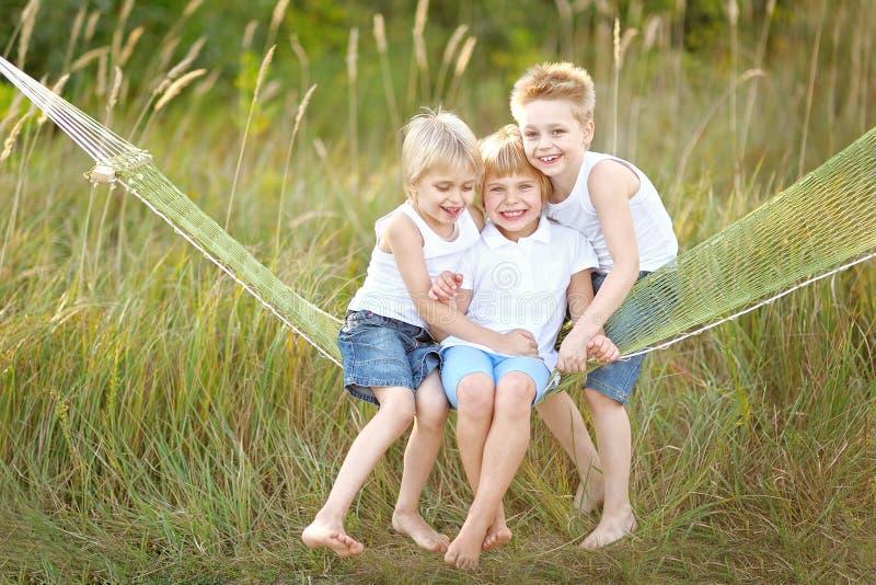 Drie kinderen lopen op een gekleurde achtergrond stock foto