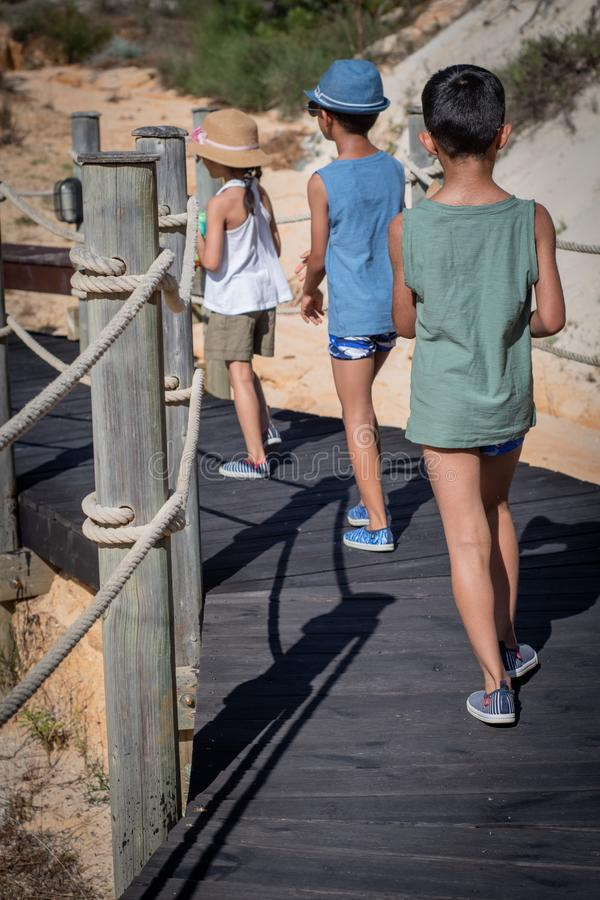 Drie kinderen op een gang op het strand royalty-vrije stock afbeelding