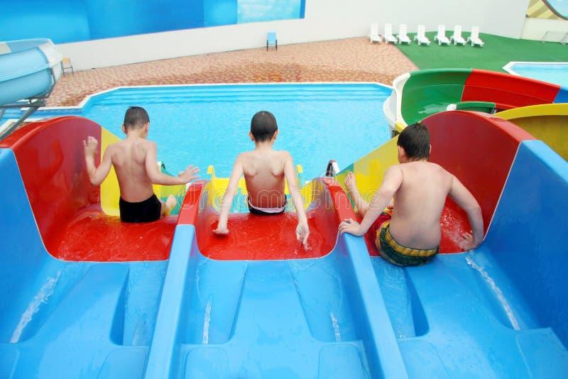 Drie kinderen treffen voorbereidingen om de heuvel in aquapark te verlaten stock fotografie