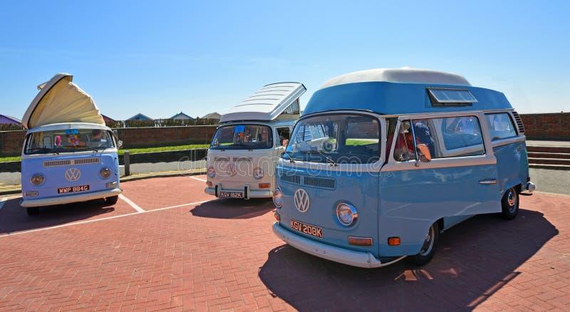 Drie Klassieke die Volkswagen Kampeerautobestelwagen samen met strandhutten wordt geparkeerd op de achtergrond stock afbeeldingen