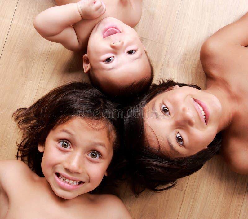 Drie kleine broers die terwijl het liggen op de vloer glimlachen royalty-vrije stock foto