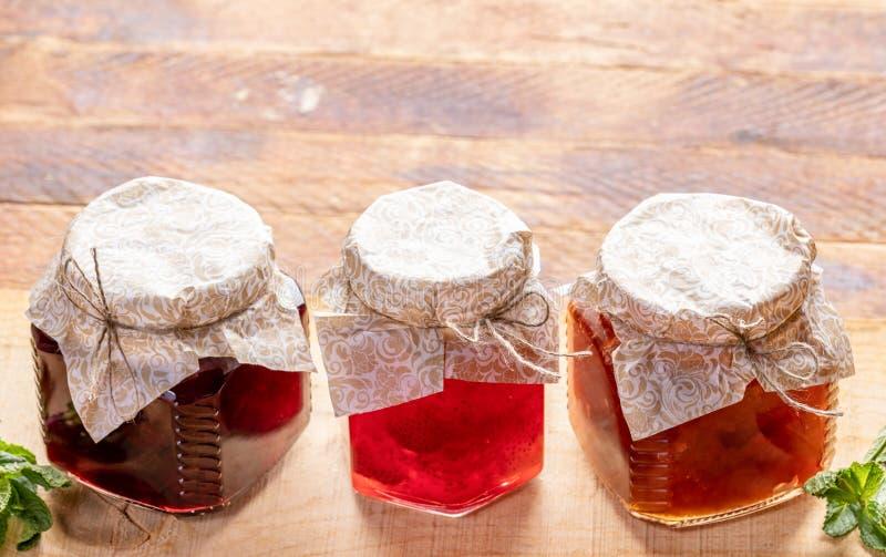 Drie kleine glaskruiken met eigengemaakte jam op houten achtergrond royalty-vrije stock afbeelding