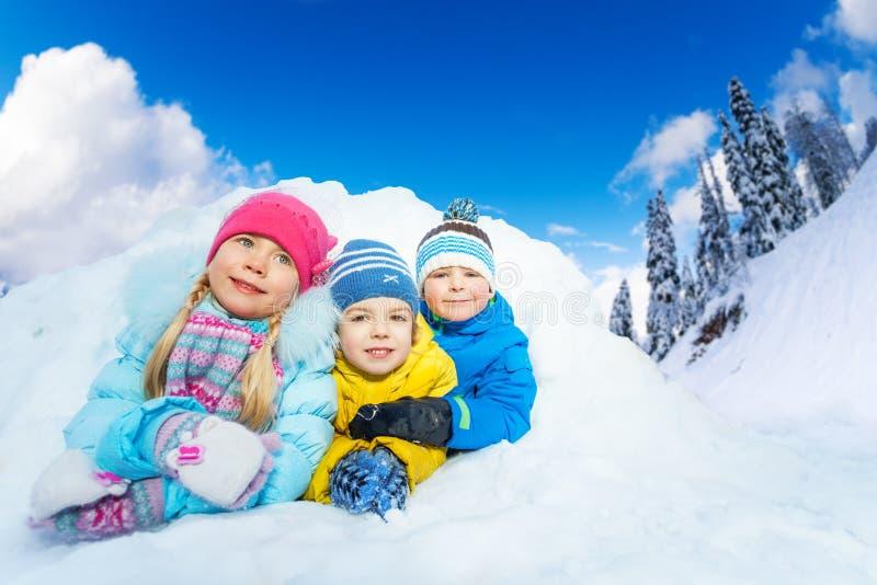 Drie kleine jonge geitjesglimlach van sneeuwhol stock foto