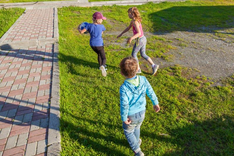 Drie kleine kinderen, twee meisjes en één jongen lopen op het groene gras in de yard tijdens de spelen, achtervolgend weg te hale stock foto