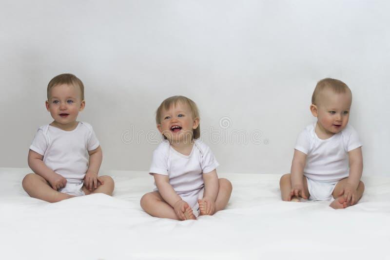 Drie kleine kinderen zitten op een witte achtergrond en een glimlach stock foto