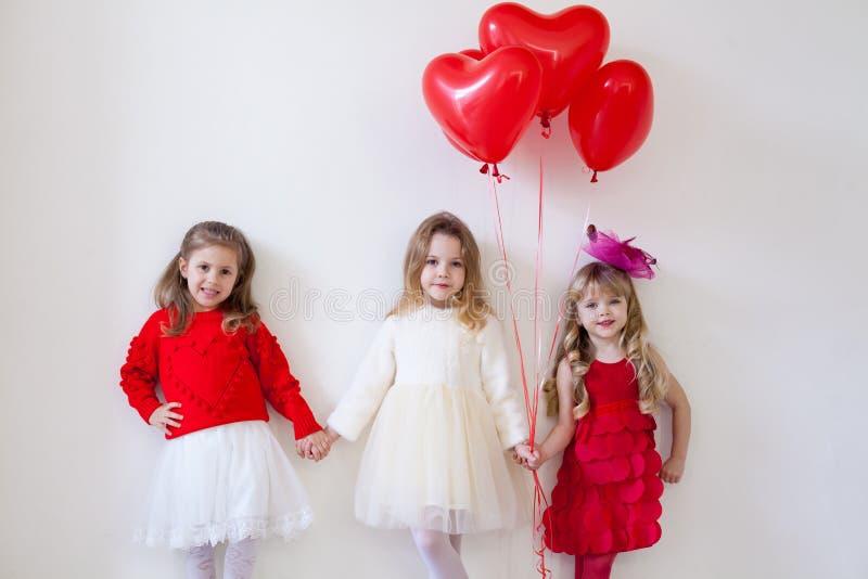 Drie kleine mooie meisjes in rode greephanden stock foto