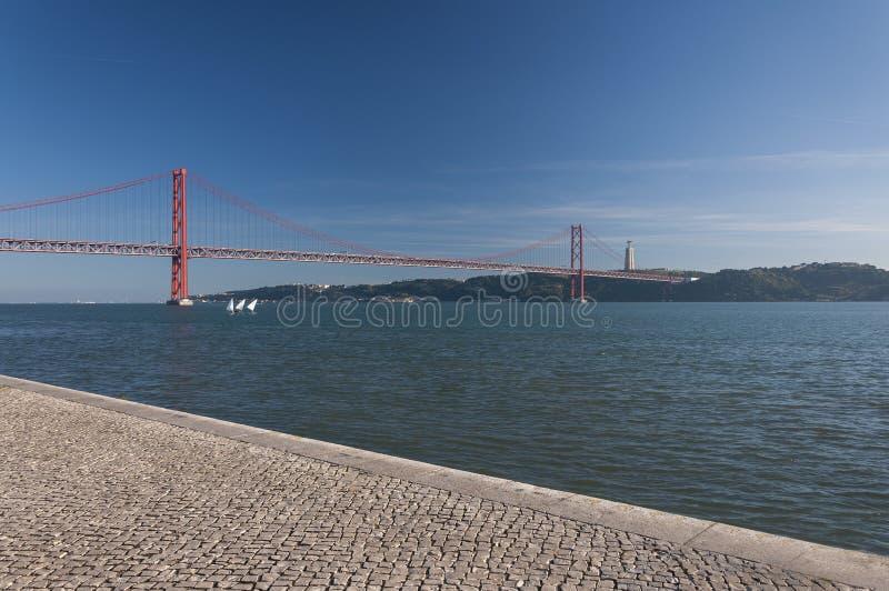 Drie kleine varende boten bij de Tagus-Rivier met 25 van April overbruggen op de achtergrond in de stad van Lissabon stock foto
