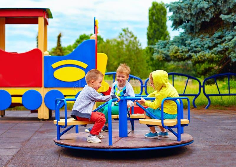 Drie kleine vrienden, jonge geitjes die pret op rotonde hebben bij speelplaats royalty-vrije stock afbeeldingen