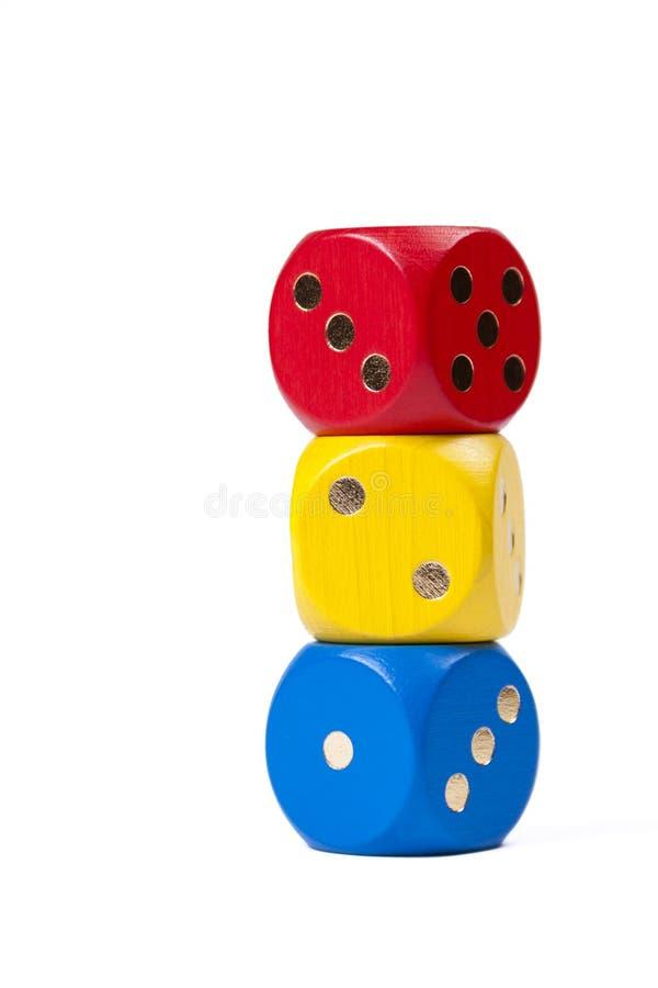 Drie kleurrijke dices in primaire kleuren gestapeld op elkaar geïsoleerd op witte achtergrond die aantallen één, twee, drie tonen stock afbeeldingen
