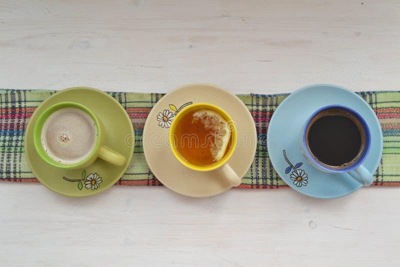 Drie kleurrijke kop theeën, cappuccino en koffieespressostoom in lijn op sjofele houten achtergrond stock afbeelding
