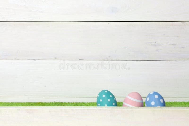 Drie kleurrijke met de hand gemaakte paaseieren bevinden zich op een groen die gazon, met een barrière, op een witte houten achte royalty-vrije stock foto