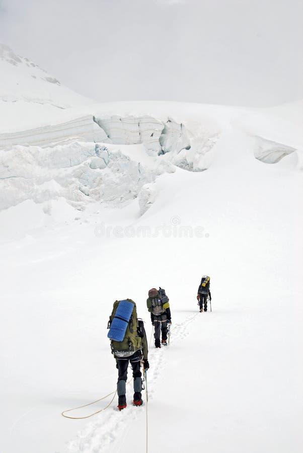 Drie klimmers op de gletsjer stock afbeeldingen