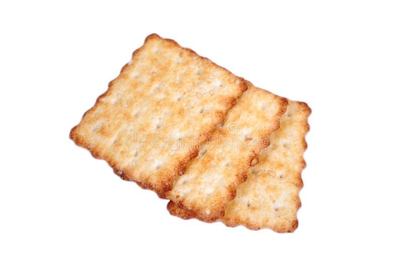 Drie koekjes van cracker met sesam liggen op een witte achtergrond Snack voor een dessert stock foto's