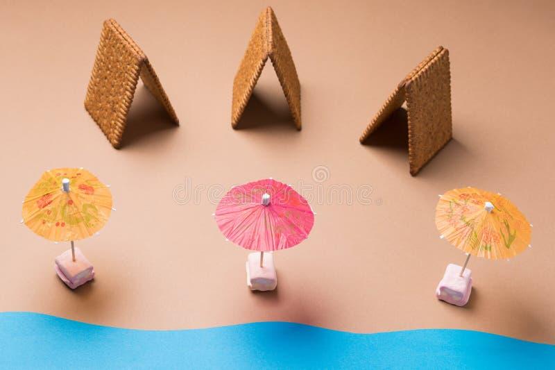 Drie koekjesbungalowwen en drie cocktailparaplu's die als een tropisch strand, vakantieconcept kijken stock foto's