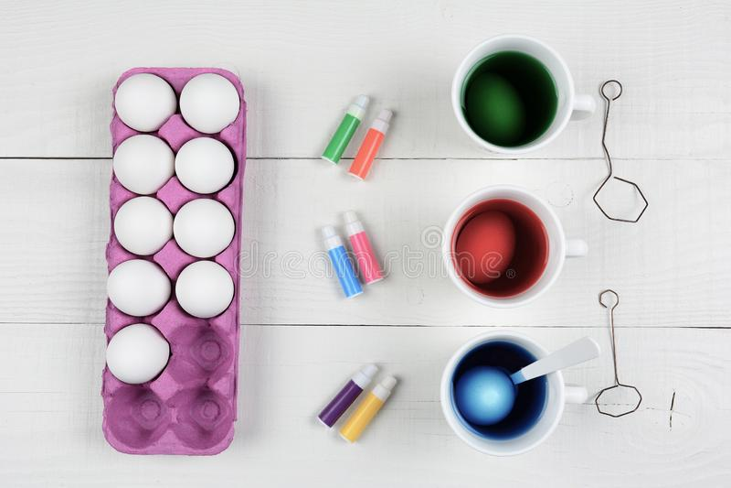 Drie koppen kleurstof en eieren met een karton van eieren en pennen voor het kleuren royalty-vrije stock afbeeldingen