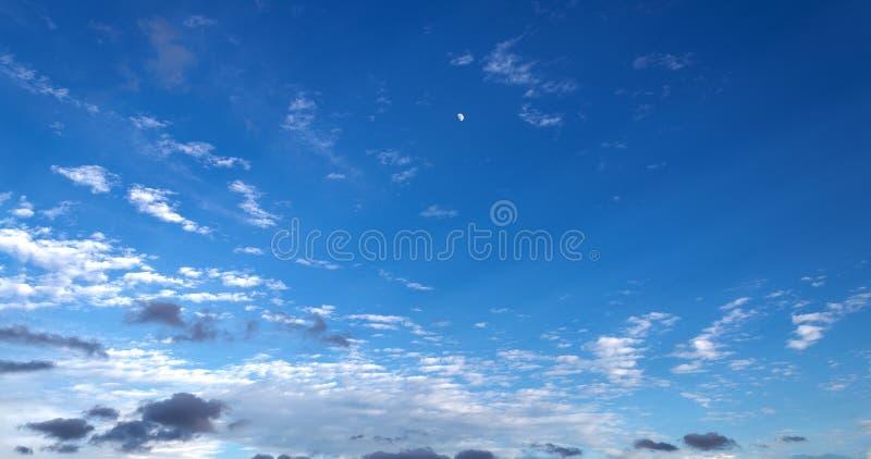 Drie kwart maan die als zonreeksen toenemen op een donkerblauwe hemel royalty-vrije stock afbeelding