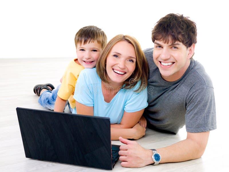 Drie lachende mensen met één laptop royalty-vrije stock fotografie