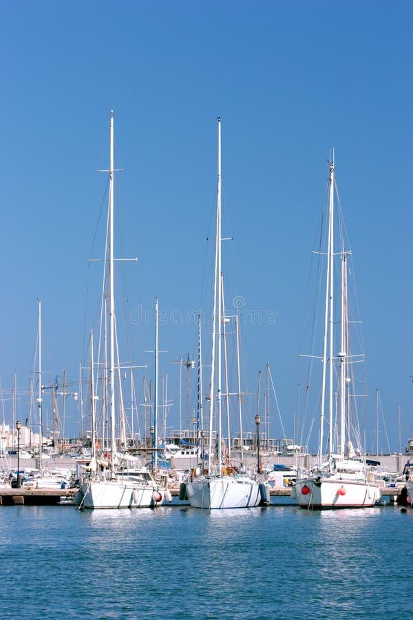 Drie lange varende schepen legden in zonnige Spaanse haven of haven vast stock foto's
