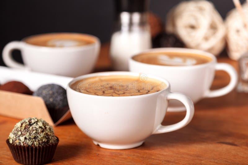Drie lattekoppen en kleine cakes op de houten lijst in de koffie Mededeling meer dan een Kop van koffie, koffiepauze stock foto