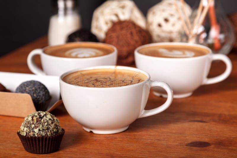 Drie lattekoppen en kleine cakes op de houten lijst in de koffie Mededeling meer dan een Kop van koffie, koffiepauze royalty-vrije stock foto