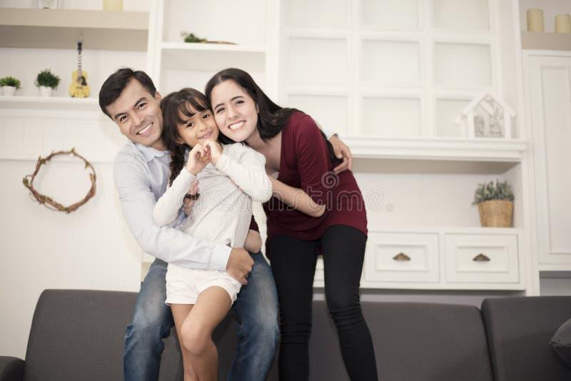 Drie leden van de Gelukkige familie in gelukkige stemming met omhelzing, het glimlachende togetherm Mamma, Papa en dochterconcept royalty-vrije stock foto's