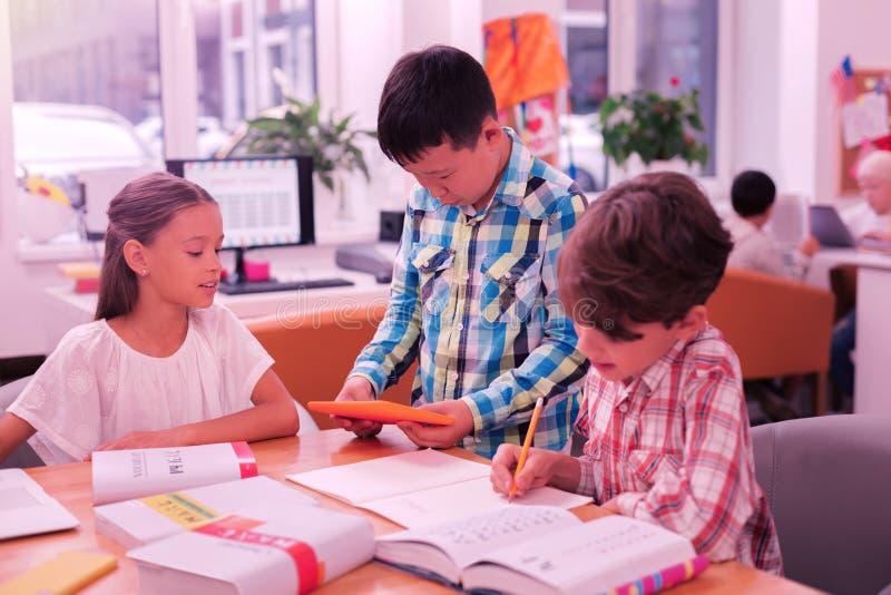 Drie leerlingen die aan hun thuiswerk samenwerken stock foto