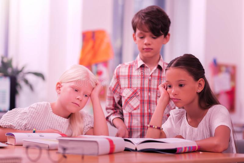 Drie leerlingen die droevig bij het bureau zitten stock afbeelding