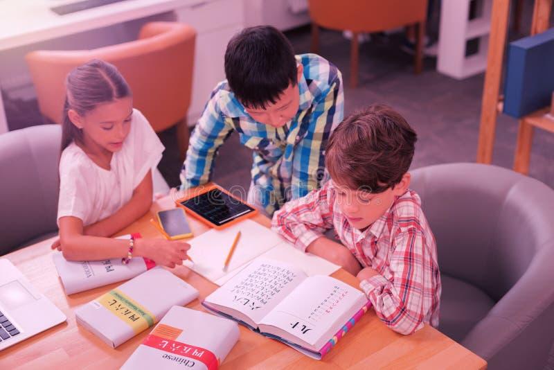 Drie leerlingen die over boeken in het klaslokaal poring royalty-vrije stock foto