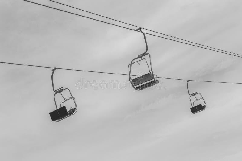 Drie lege liftstoel tegen de hemel stock afbeeldingen