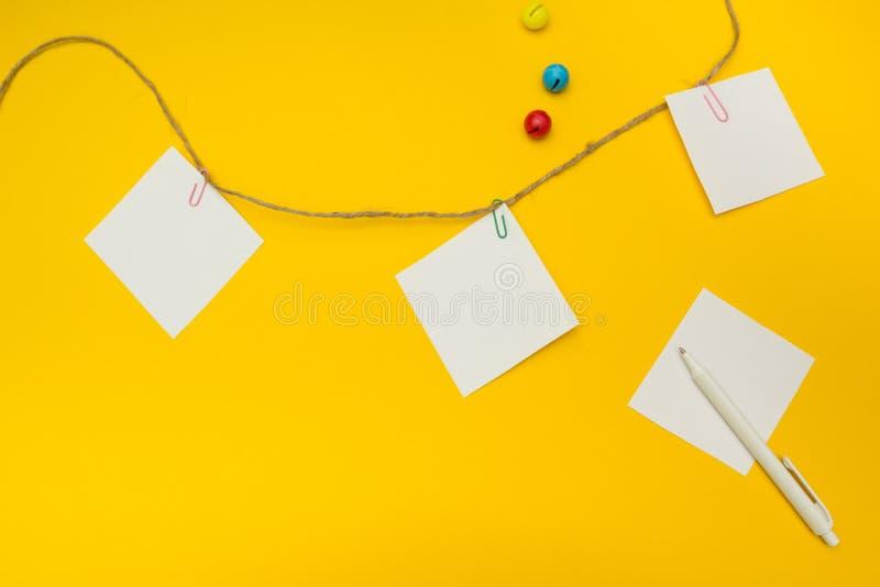 Drie lege notadocumenten in bijlage aan een kabel op een gele achtergrond stock foto's