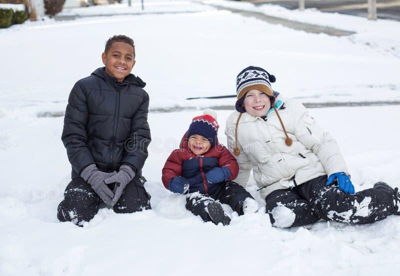 Drie leuke diverse jongens die samen in de sneeuw in openlucht spelen stock afbeeldingen