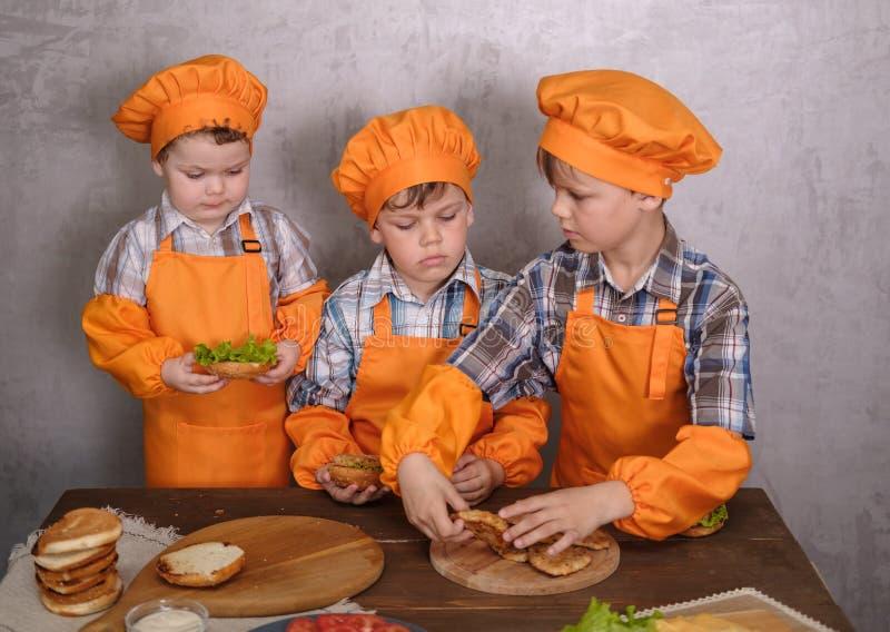 Drie leuke jongens in kostuumskoks belast met het koken eigengemaakte burgers stock afbeelding