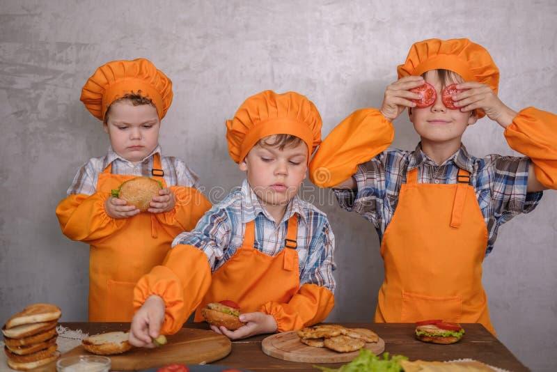 Drie leuke jongens in kostuumskoks belast met het koken eigengemaakte burgers royalty-vrije stock foto's