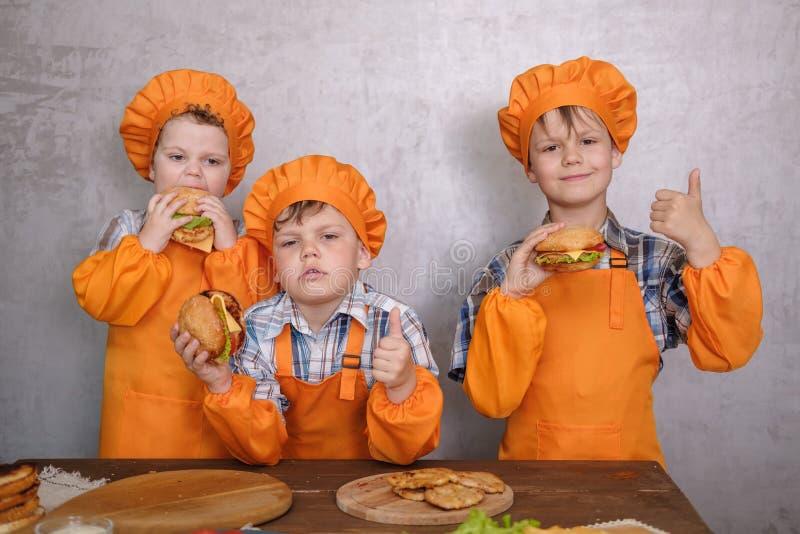 Drie leuke jongens in kostuumskoks belast met het koken eigengemaakte burgers royalty-vrije stock fotografie