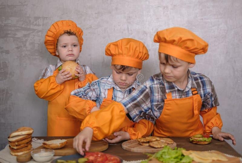 Drie leuke jongens in kostuumskoks belast met het koken eigengemaakte burgers stock foto