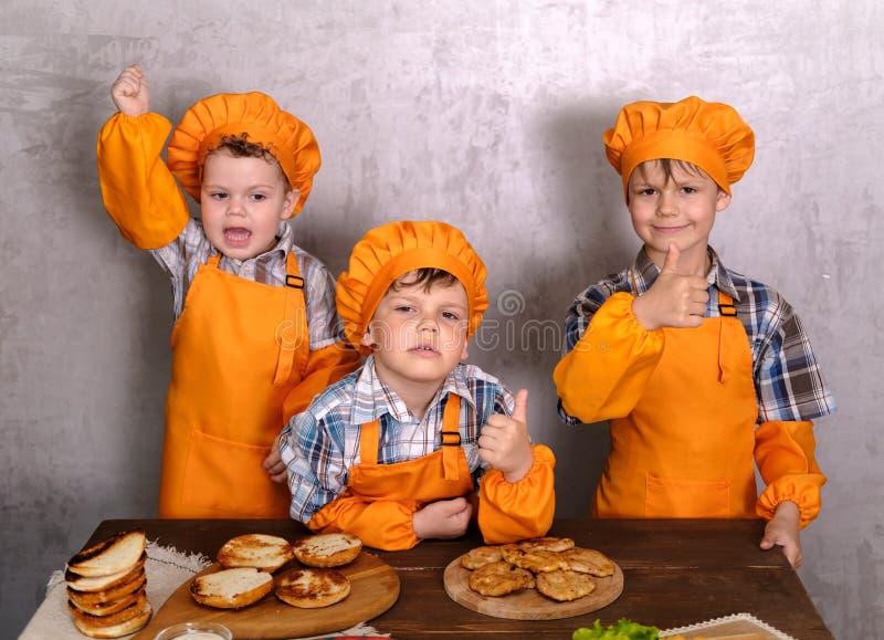 Drie leuke jongens in kostuumskoks belast met het koken eigengemaakte burgers stock foto's