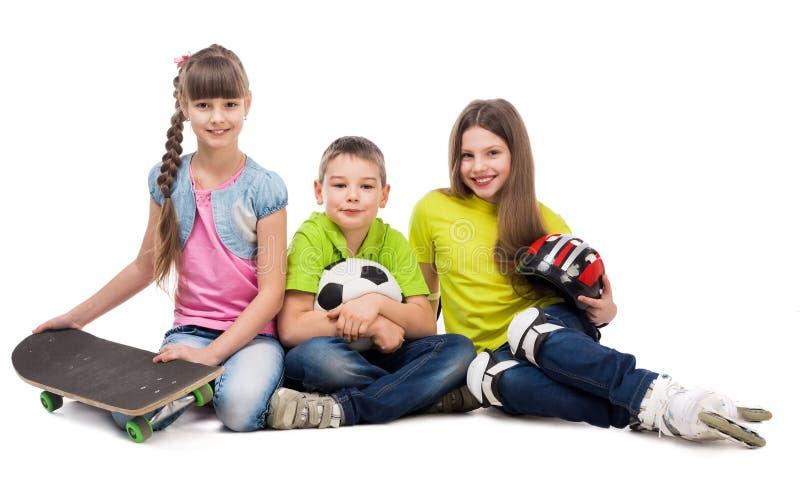 Drie leuke kinderen die op de vloer met sportmateriaal zitten royalty-vrije stock afbeeldingen